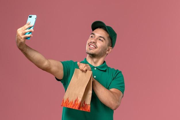 Vue avant de courrier masculin en uniforme vert tenant le paquet de nourriture et de prendre une photo avec elle sur le fond rose