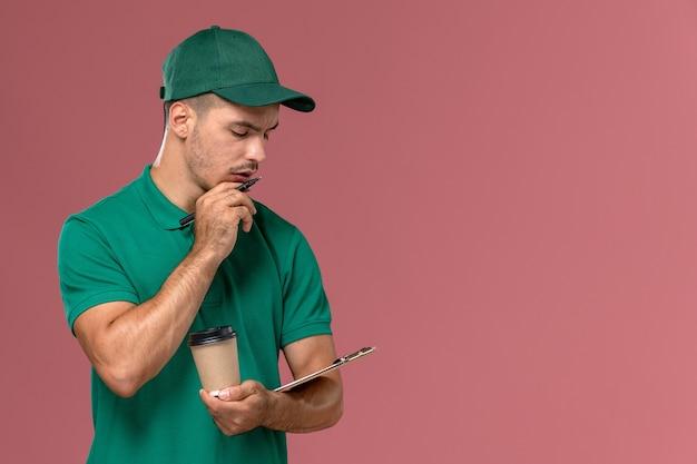 Vue avant de courrier masculin en uniforme vert tenant la tasse de café de livraison et le bloc-notes pensant sur le bureau rose clair