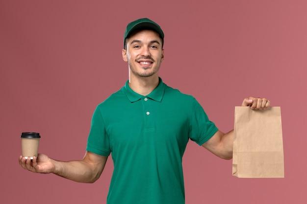 Vue avant de courrier masculin en uniforme vert tenant la tasse de café de livraison et le paquet de nourriture sur le bureau rose clair