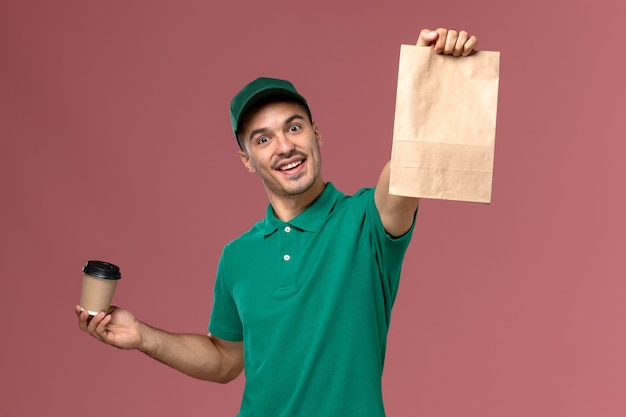 Vue avant de courrier masculin en uniforme vert tenant la tasse de café de livraison et le paquet de nourriture sur le fond rose clair