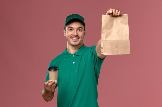 Vue avant de courrier masculin en uniforme vert tenant la tasse de café de livraison et le paquet de nourriture avec le sourire sur fond rose clair