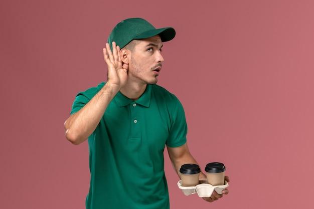 Vue avant de courrier masculin en uniforme vert tenant des tasses de café de livraison brun essayant d'entendre sur fond rose
