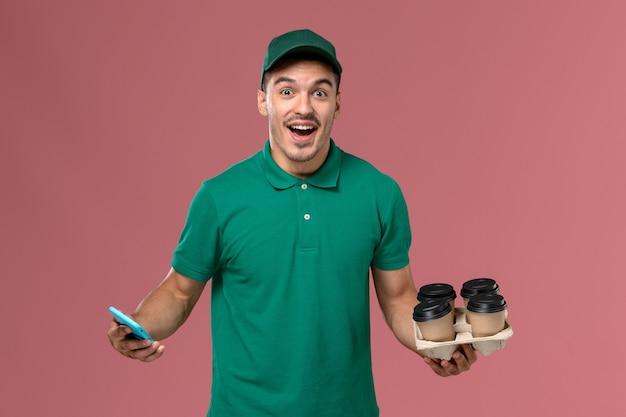 Vue avant de courrier masculin en uniforme vert tenant des tasses à café marron et téléphone sur fond rose