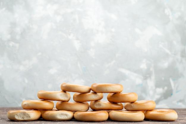 Vue avant des craquelins ronds sucrés séchés et des collations savoureuses sur blanc, boisson biscuit biscuit