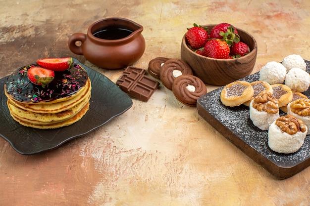 Vue avant des crêpes sucrées avec des bonbons et des biscuits sur le gâteau de bureau en bois tarte dessert sucré