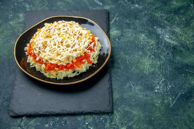 Vue avant de la délicieuse salade de mimosa à l'intérieur de la plaque sur une surface bleu foncé cuisine photo cuisine anniversaire repas de vacances couleur nourriture viande
