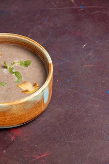 Vue avant de la délicieuse soupe aux champignons à l'intérieur de la plaque sur l'espace sombre