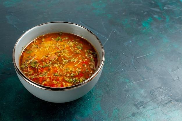 Vue avant de la délicieuse soupe aux légumes à l'intérieur de la plaque sur une surface vert foncé