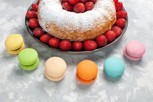 Vue avant de la délicieuse tarte aux fraises avec des macarons sur blanc clair