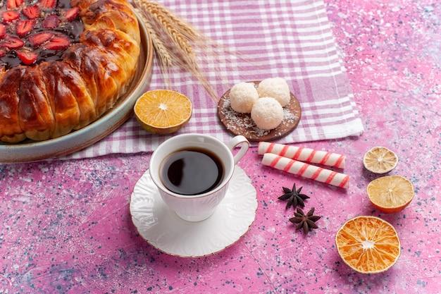 Vue avant de la délicieuse tarte aux fraises ronde gâteau fruité formé sur rose vif