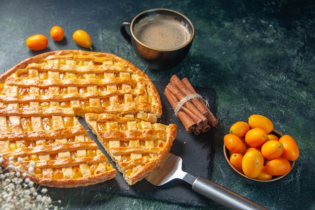 Vue avant de la délicieuse tarte kumquat avec une pièce en tranches et du café sur une surface sombre dessert au four pâtisserie douce pâte biscuit gâteau au thé couleur biscuit