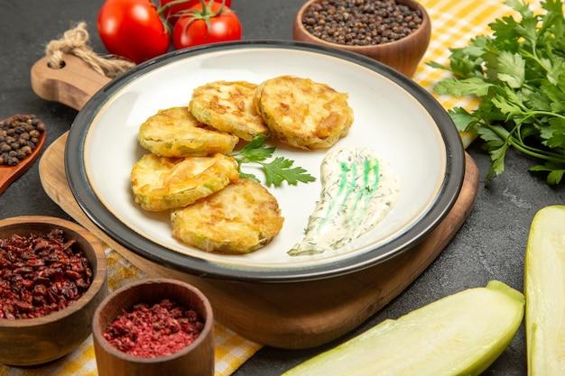 Vue avant de délicieuses courges cuites avec assaisonnements et tomates sur espace gris