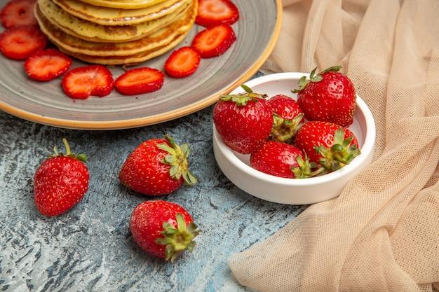 Vue avant de délicieuses crêpes aux fraises fraîches sur une surface légère aux fruits gâteau sucré