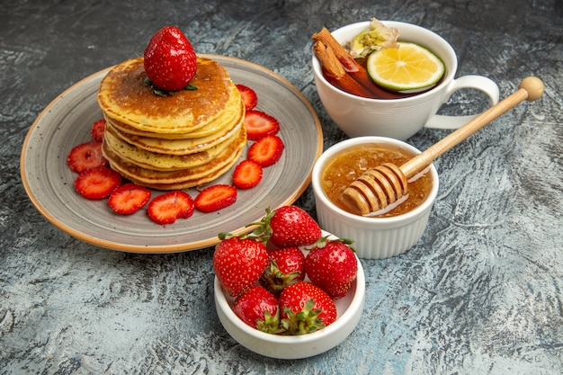 Vue avant de délicieuses crêpes aux fraises et tasse de thé sur la surface légère gâteau aux fruits sucré