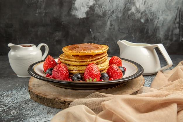 Vue avant de délicieuses crêpes aux fruits et miel sur une surface légère au lait de fruits sucré