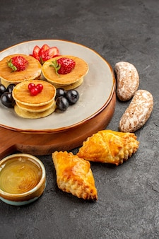 Vue avant de délicieuses crêpes aux olives et gâteaux sur la surface sombre gâteau sucré aux fruits