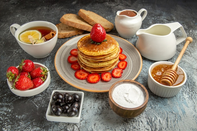 Vue avant de délicieuses crêpes avec du thé et des fruits sur la surface légère gâteau aux fruits sucré