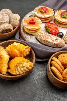 Vue avant de délicieuses crêpes avec des fruits et des gâteaux sucrés sur la surface sombre gâteau dessert sucré