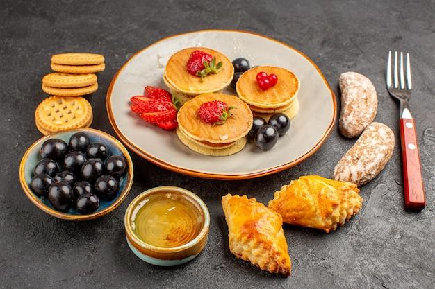 Vue avant de délicieuses crêpes avec des gâteaux et des fruits sur la surface sombre gâteau sucré aux fruits