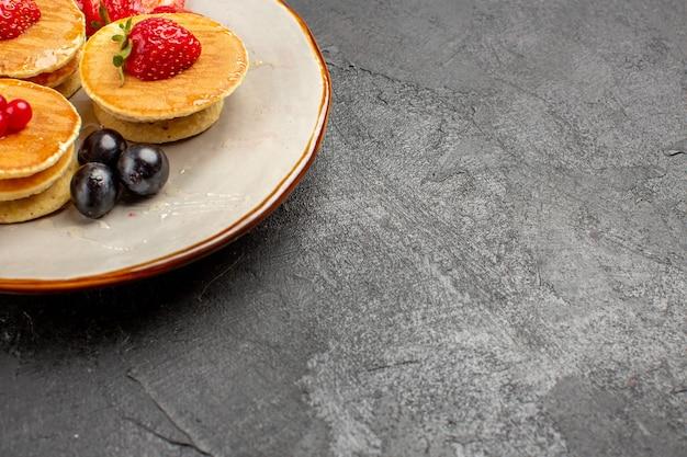 Vue avant de délicieuses crêpes peu formées avec des fruits sur la tarte aux fruits de surface grise