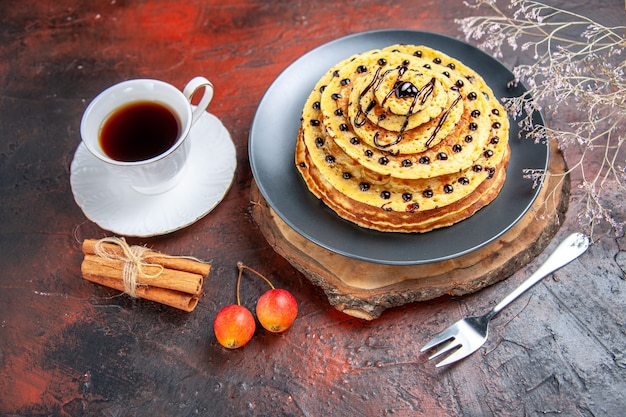Vue avant de délicieuses crêpes sucrées avec du thé sur fond sombre