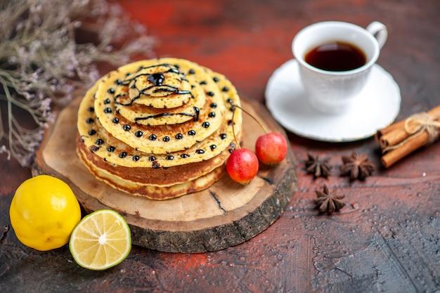 Vue avant de délicieuses crêpes sucrées avec tasse de thé sur un bureau sombre
