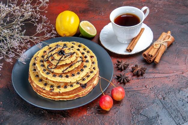 Vue avant de délicieuses crêpes sucrées avec tasse de thé sur fond sombre gâteau dessert sucré lait