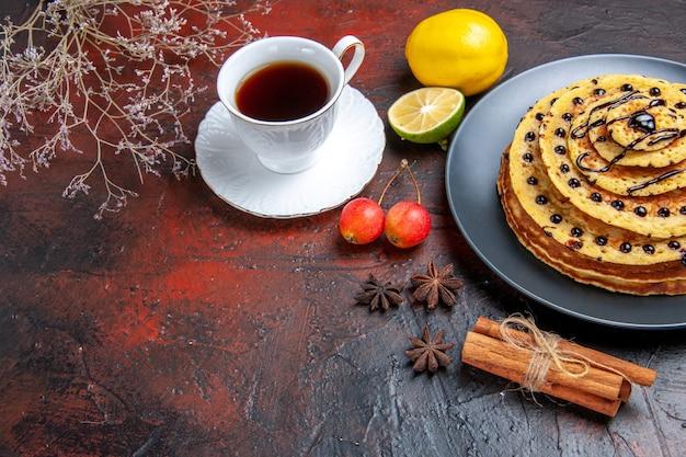 Vue avant de délicieuses crêpes sucrées avec tasse de thé sur fond sombre