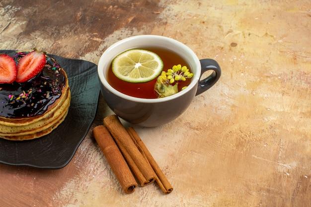 Vue avant de délicieuses crêpes sucrées avec une tasse de thé sur un gâteau de bureau léger