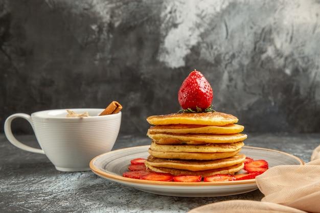 Vue avant de délicieuses crêpes avec une tasse de thé et de fruits sur une surface légère gâteau aux fruits sucrés