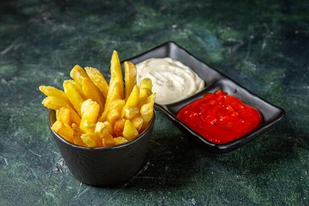 Vue avant de délicieuses frites avec des assaisonnements sur une surface sombre