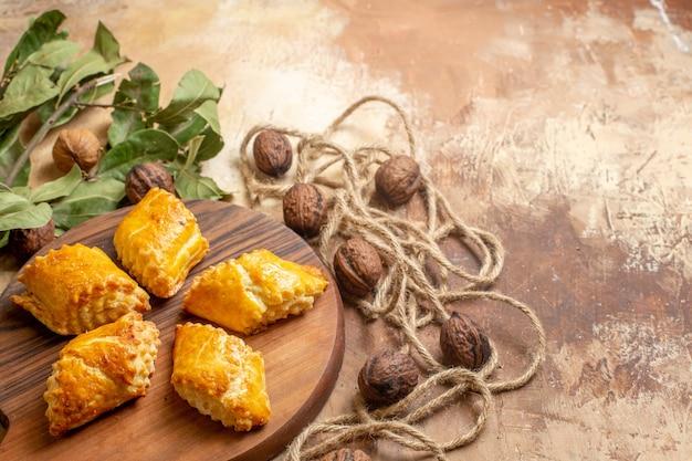Vue avant de délicieuses pâtisseries aux noix avec des noix sur brown desk cake pâtisseries tartes aux noix sucrées