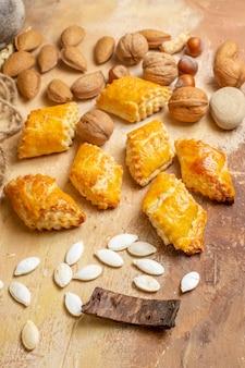 Vue avant de délicieuses pâtisseries aux noix avec des noix fraîches sur la pâtisserie gâteau de table brune aux noix de tarte sucrée