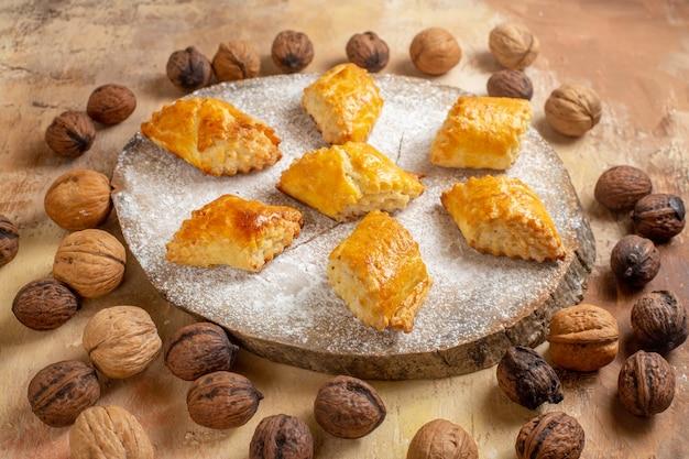 Vue avant de délicieuses pâtisseries aux noix avec des noix sur table lumineuse gâteau pâtisserie tarte sucrée