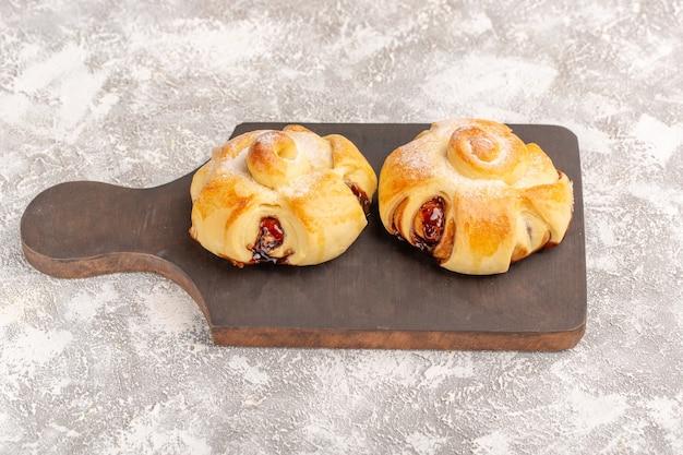 Vue avant de délicieuses pâtisseries fruitées sucrées cuites au four sur gris bureau gâteau pâtisserie sweet bake tea