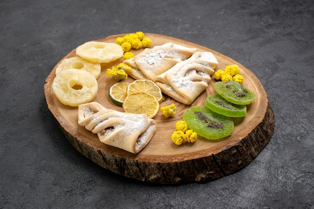 Vue avant de délicieuses pâtisseries avec des tranches de fruits secs sur l'espace gris