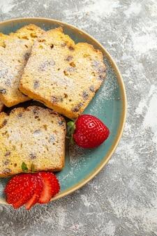 Vue avant de délicieuses tranches de gâteau aux fruits sur la tarte de bureau léger gâteau aux fruits sucré