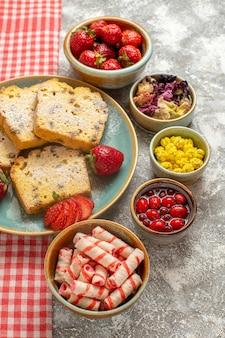 Vue avant de délicieuses tranches de gâteau avec des fraises fraîches sur la tarte au sol léger fruits sucrés