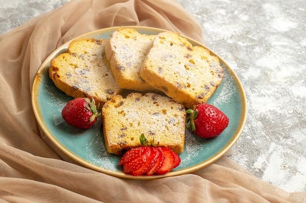 Vue avant de délicieuses tranches de gâteau avec des fraises fraîches sur la tarte aux fruits de surface légère