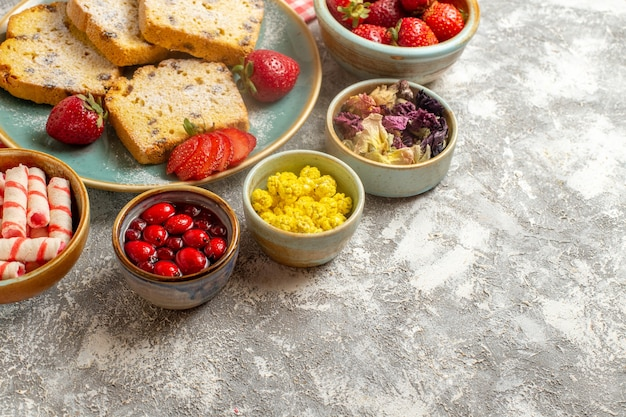 Vue avant de délicieuses tranches de gâteau avec des fraises fraîches sur une tarte à surface légère aux fruits sucrés