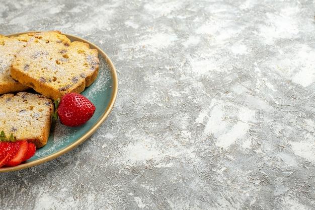 Vue avant de délicieuses tranches de gâteau avec des fruits sur la surface légère gâteau aux fruits tarte douce