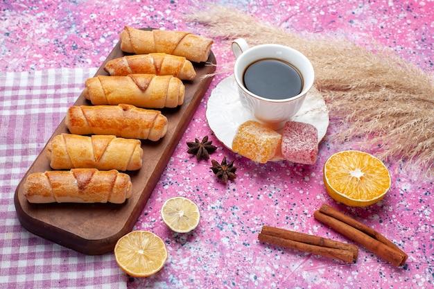 Vue avant de délicieux bagels à la cannelle et tasse de thé sur un bureau rose.