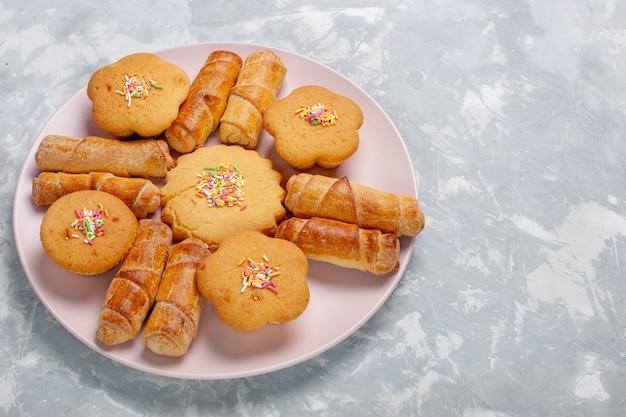 Vue avant de délicieux bagels avec des gâteaux à l'intérieur de la plaque sur un bureau blanc clair