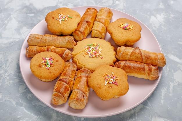 Vue avant de délicieux bagels avec des gâteaux à l'intérieur de la plaque sur un bureau blanc