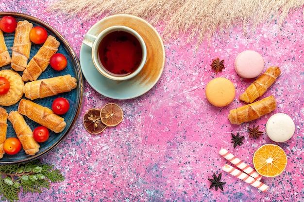 Vue avant de délicieux bagels sucrés avec des macarons français et une tasse de thé sur un bureau rose clair