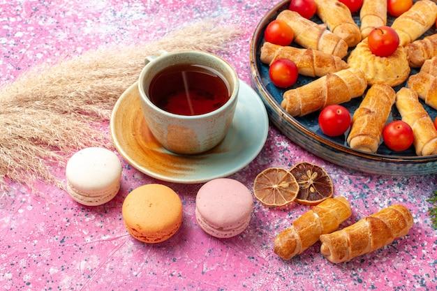 Vue avant de délicieux bagels sucrés avec des prunes aigres fraîches macarons français et tasse de thé sur un bureau rose clair
