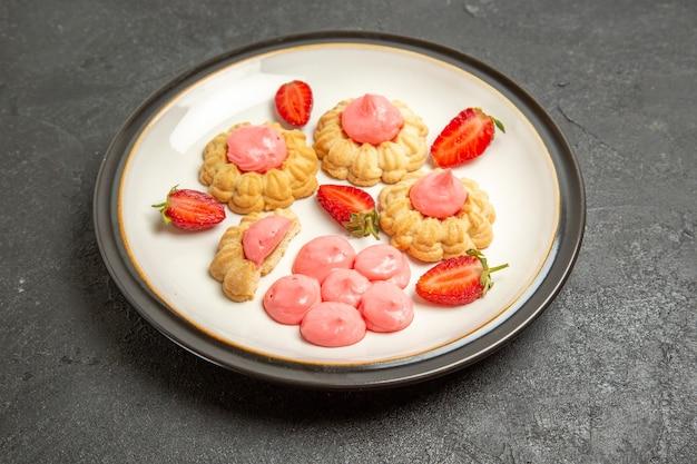 Vue avant de délicieux biscuits au sucre avec de la gelée de fraise sur l'espace gris