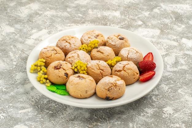 Vue avant de délicieux biscuits au sucre à l'intérieur de la plaque sur fond blanc biscuit au sucre biscuit sucré gâteau thé