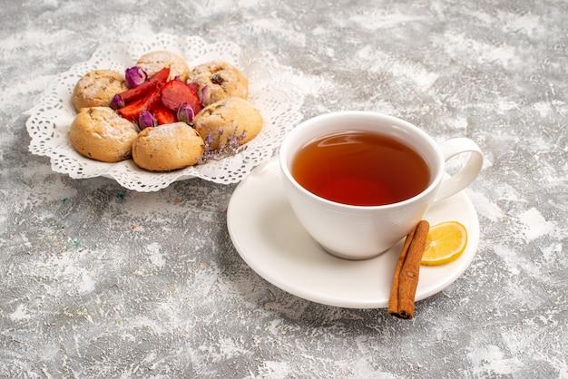 Vue avant de délicieux biscuits de sable avec des fraises fraîches et une tasse de thé sur un espace blanc