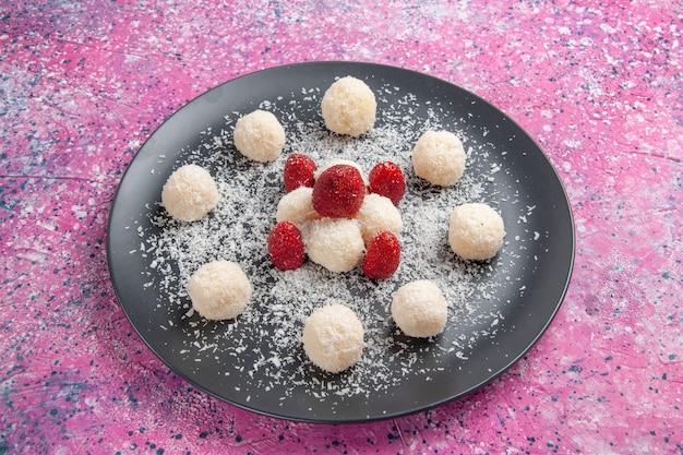 Vue avant de délicieux bonbons à la noix de coco boules sucrées sur mur rose